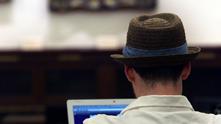 Мъж с шапка и компютър