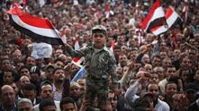 Дете във военна униформа развява знамето на Египет
