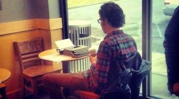 Хипстър твори на пишеща машина в Starbucks