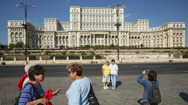 Туристи се снимат пред парламента на Румъния, който се помещава в Двореца на Народа, построен от Чаушеску