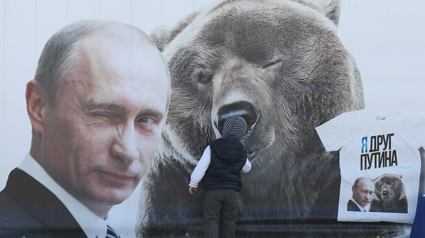 Момче пред плакат на Путин с мечка