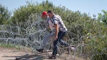 мигранти прескачат оградата от бодлива тел по унгарската граница