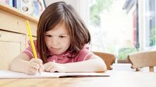 Момиче пише в тетрадка